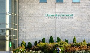 A man walks past the University of Vermont health network building